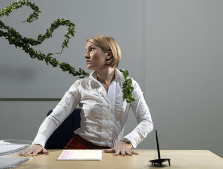 Woman by desk beeing attacked by plants LANG_EVOIMAGES