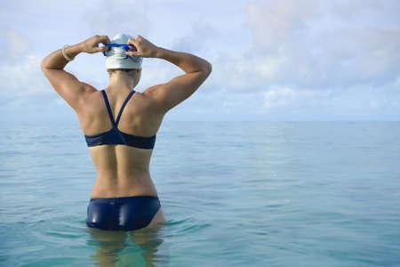Woman preparing for swim in tropical sea