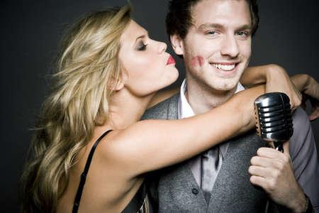 smooching: girl kissing man with mic