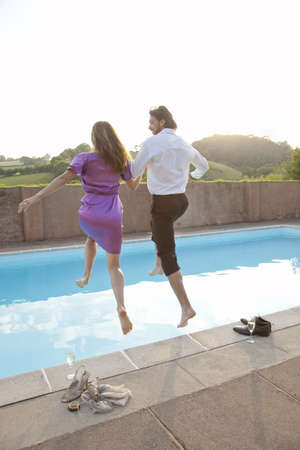 mischievious: couple jumping into pool,dressed LANG_EVOIMAGES
