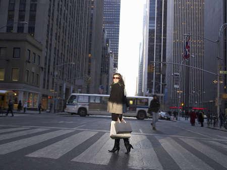 motorcoach: Elegant woman crossing New York street LANG_EVOIMAGES