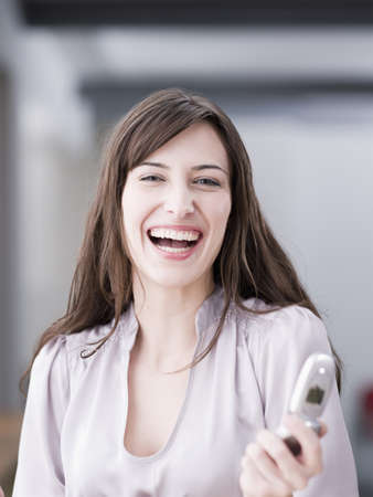 Woman laughing at viewer holding phone LANG_EVOIMAGES