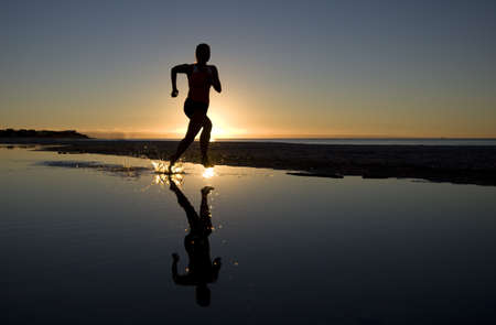 Young Woman Running on Beach at Sunset