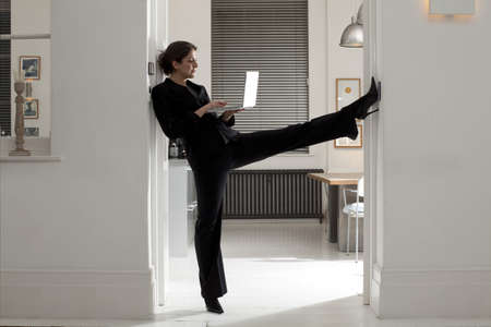 motivations: woman stretching with laptop LANG_EVOIMAGES