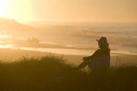 forties: Woman watches Sunset on Beach LANG_EVOIMAGES