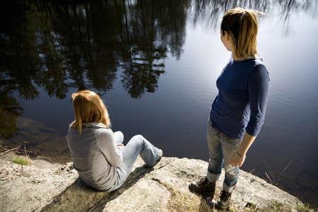 Two women looking at lake