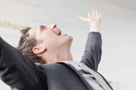 accomplishes: Man raising his arms in joy