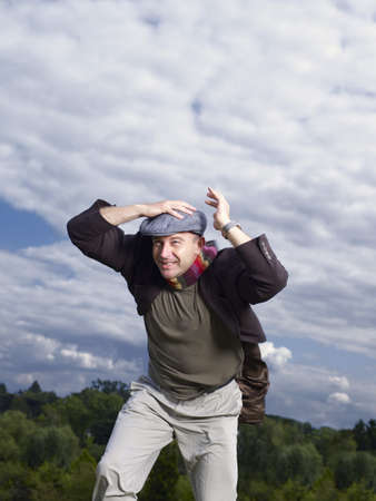 survives: Man holding onto hat in wind