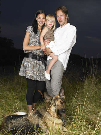 Family with dog in a field,  by night