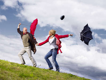 survives: Couple with umbrellas in wind LANG_EVOIMAGES