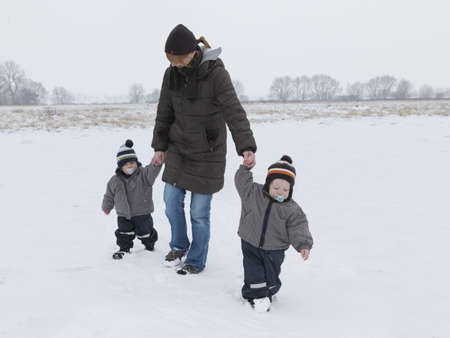 dependencies: Woman walking with twin sons in snow LANG_EVOIMAGES