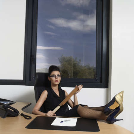 aggressively: Businesswoman holding a cricket bat