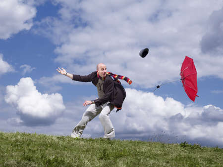 survives: Man losing hat and umbrella in wind LANG_EVOIMAGES