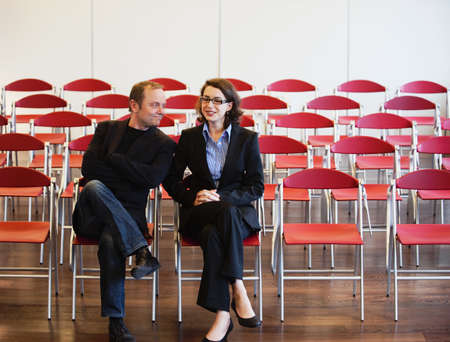aggressively: businessman, woman among empty chairs