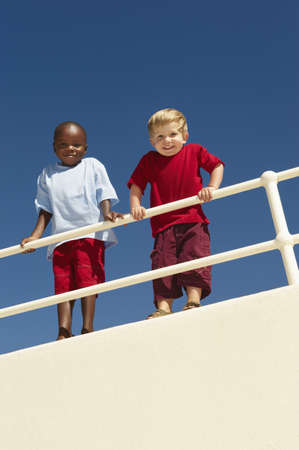 southern european descent: Young boys leaning over railing