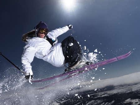 sun energy: Man grabbing ski tail mid air. LANG_EVOIMAGES