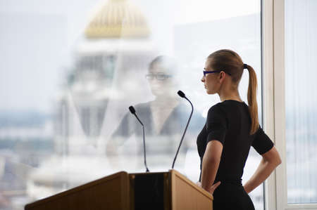 musing: Woman in a conference room, with a view LANG_EVOIMAGES