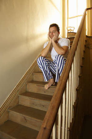 struggled: Man sitting on stairs in his pajamas LANG_EVOIMAGES