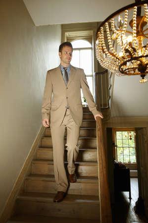lavishly: Man in suit walking down staircase