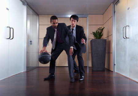 confrontational: Businessmen playing basketball in office LANG_EVOIMAGES