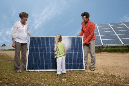 obligations: family in front of solar panel LANG_EVOIMAGES