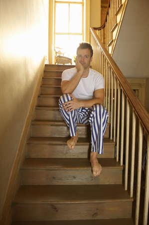 nightwear: Man sitting on stairs in his pajamas LANG_EVOIMAGES