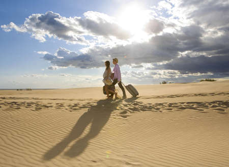 hardships: Traveling couple walking on sand