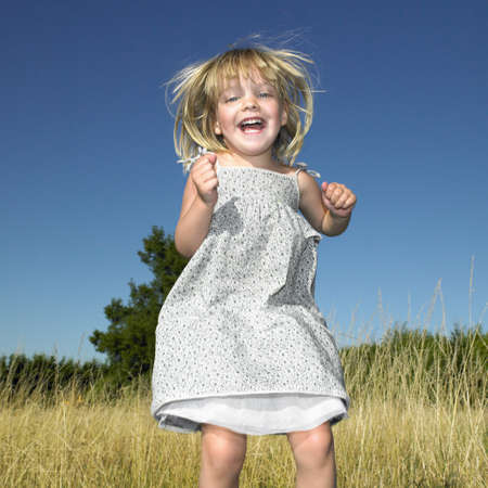uncomplicated: Girl jumping in a field LANG_EVOIMAGES
