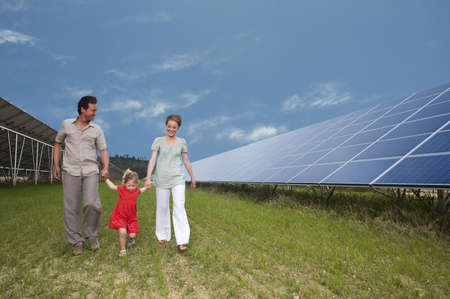 family walking along solar panel LANG_EVOIMAGES