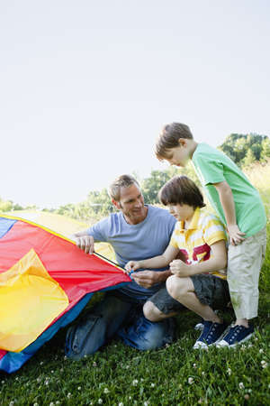 Boys And Father Building Tent