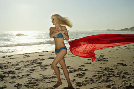 joyous: Young girl throwing sarong on a beach LANG_EVOIMAGES