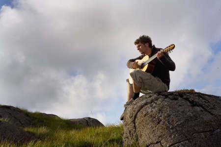 Young man playing guitar in landscape LANG_EVOIMAGES