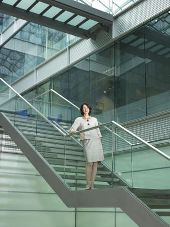 accomplishes: Woman standing on stairs LANG_EVOIMAGES