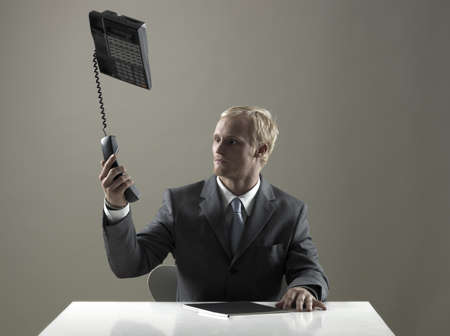 acknowledging: Business man holding phone in mid-air