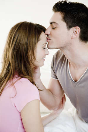 smooching: Young couple lying on bed