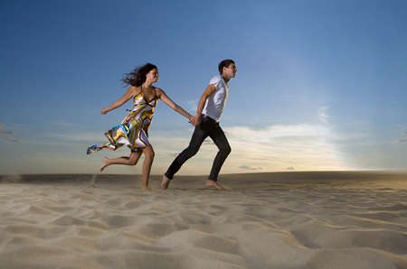 pursuing: Couple running on beach LANG_EVOIMAGES