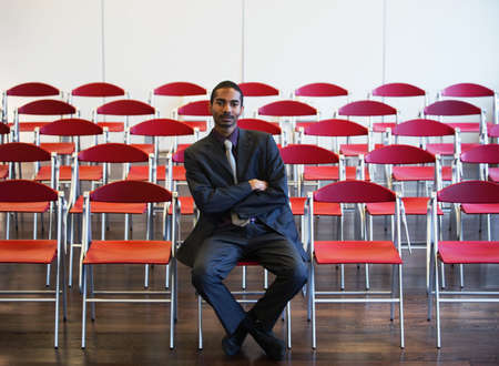 Black businessman among empty chairs