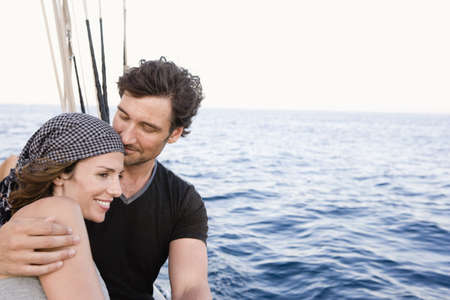 adventuresome: couple standing at rail of sailing boat LANG_EVOIMAGES