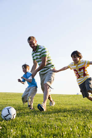 pas: Father and Two Sons Playing Soccer