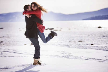 Man picking up woman on snowy beach
