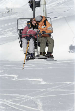 Couple sitting on chair lift,  kissing