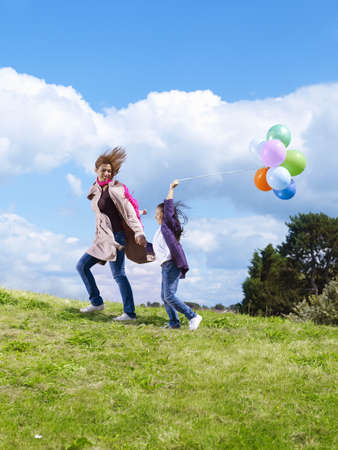 Mother & daughter with balloons in wind LANG_EVOIMAGES