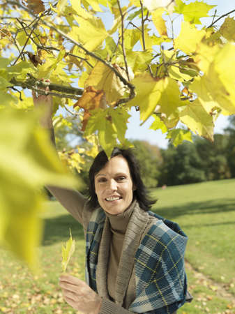 Woman looking through Autumn branches LANG_EVOIMAGES