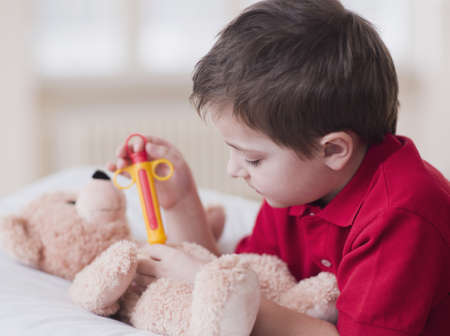 boy playing with toy and teddy bear