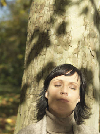 basking: Woman leaning against tree in sunshine