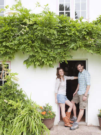 couple by front door of house LANG_EVOIMAGES