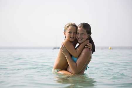 Girl hugging little girl in ocean LANG_EVOIMAGES