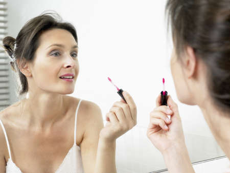 maquillage: Woman in bathroom, applying makeup