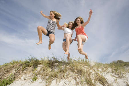 joyous: Teenage Girls jumping on Beach