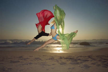 Dancers leaping on a beach